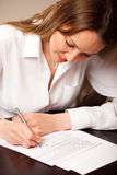 Signing contract. Attractive young woman signing contract Stock Photography