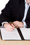 Signing the contract. A business man in a blue suit and no tie signing a contract Royalty Free Stock Photo