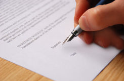 Signing contract. Close-up of a male hand signing a business contract with a fountain pen stock image