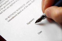 Signing contract. Close-up of a hand signing a contract with a fountain pen royalty free stock photography