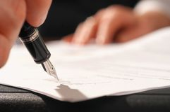 Signing a contract. Close up of a hand signing a contract Stock Image