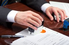 Signing contract. Notary public signing document at his workplace Royalty Free Stock Images