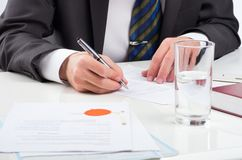 Signing contract. Notary public signing document at his workplace royalty free stock photo