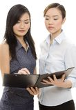 Signing The Contract. Two asian businesswomen sign a document in a black clipboard Stock Images