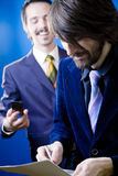 Signing a contract. Two happy young businessmen signing a contract Stock Photo