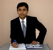 Signing a contract. Handsome Indian businessman signing a contract Stock Photos