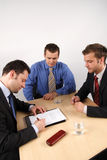 Signing a contract. A businessman signing a contract. Two other businessmen watch him Royalty Free Stock Images