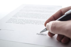 Signing a contract. Male hand signing a contract above signature line Royalty Free Stock Photos