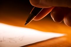 Signing contract. A closeup view of the fingers of a hand holding an ink pen, about to sign a contract