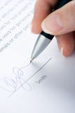 Signing of the contract. The woman signs the contract a ball pen Stock Photography