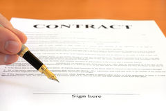 Signing contract. Male hand holding fountain pen pointing at signature place on a contract document Stock Photography