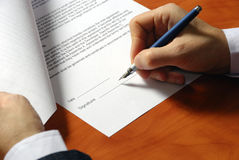 Signing a contract. Close up on a businessman hands signing a contract Stock Images