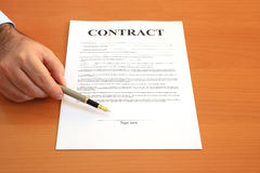 Signing contract. Male hand holding fountain pen pointing at signature place on a contract document (fictitious legal text Royalty Free Stock Photo
