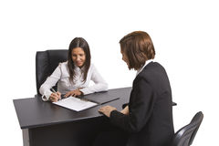 Signing the contract. Two businesswomen signing a contract in the office. All the documents are mine Stock Photography