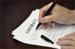 Signing a Contract. Business man signing contract with black pen on desk Royalty Free Stock Images