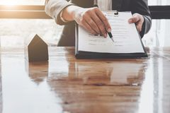 Signing contract. Close-up of confident young man signing some d. Ocument while another man in shirt and tie sitting close to him and pointing document Royalty Free Stock Photography