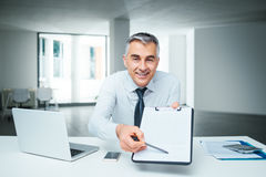Signing a contract. Confident businessman at desk handing a clipboard and a pen, contract signature and agreement concept Royalty Free Stock Images