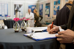 Signing a contract on a fair. Focus on hand Stock Photos