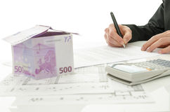 Signing contract of house sale. With house made of 500 Euro money and  architectural building plan on a white table Royalty Free Stock Photos