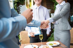 Signing a contract. Image of businesspeople handshaking after signing a contract during a lunch Royalty Free Stock Photos