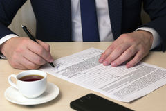 Signing a contract man , coffee , phone Stock Photo