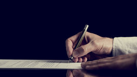 Signing a contract over dark background Royalty Free Stock Photos