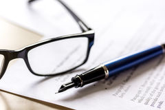 Signing the contract with pen and glasses in business work on office desk Royalty Free Stock Image