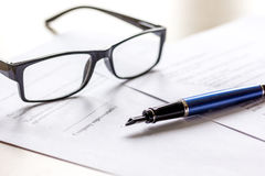 Signing the contract with pen and glasses in business work on office desk Royalty Free Stock Images