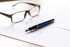 Signing the contract with pen and glasses in business work on office desk Royalty Free Stock Photography