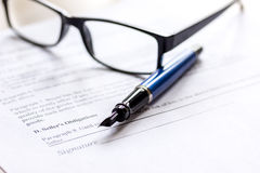 Signing the contract with pen and glasses in business work on office desk Stock Images
