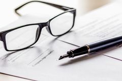 Signing the contract with pen and glasses in business work on of. Fice desk background Stock Images