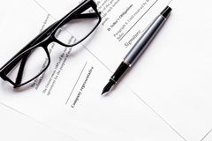 Signing the contract with pen and glasses in business work top v. Signing the contract with pen and glasses in business work on office desk background top view Royalty Free Stock Photo