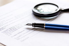 Signing the contract with pen and magnifier in business work on office desk Stock Images