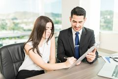 Signing Contract To Build Better Business Relationships. Satisfied businesswoman signing contract after successful negotiation during meeting at office royalty free stock image