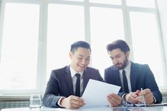 Before signing contract. Two partners reading contract at office Royalty Free Stock Photos