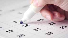 Signing a day on the calendar. Signing a day on a calendar with blue pen or marker. Putting date in circle. Valentine`s day stock video footage