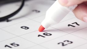 Signing a day on the calendar. Signing a day on a calendar with red pen or marker. Putting date in circle stock footage