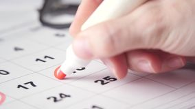Signing a day on the calendar. Signing a day on a calendar with red pen or marker. Putting date in circle stock video footage
