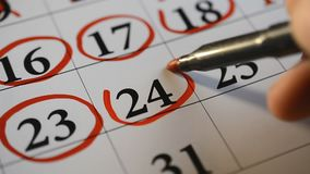 Signing a day on a calendar by red pen. Twenty four and twenty five number stock video
