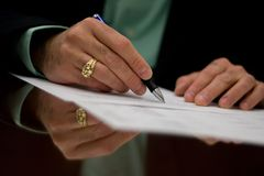 Signing the Deal. A business man signs an agreement royalty free stock image