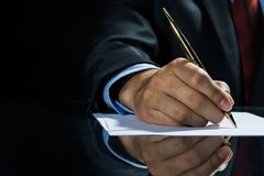 Signing a deal!. Close up of businessman sitting at table and signing document royalty free stock photos