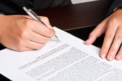 Signing a Document. Businesswoman signing a document on a dark table Stock Photo