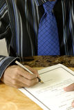 Signing a document. An image of a person signing a document Stock Image