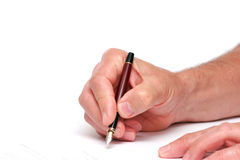 Signing a document. Someone signing a document with a fountain pen isolated on a white background stock photos