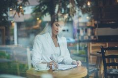 Signing document. Business woman writing on document at cafe royalty free stock image