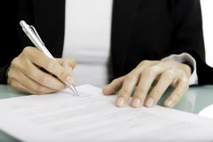 Signing a document. Closeup of a woman hands signing a document - focus on the right hand and the pen Royalty Free Stock Image