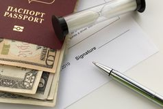 Signing a document. Passport of Russian Federation with US dollars banknotes,. Sand glass and pen. Topics of rent a car, car sharing, insurance compensation royalty free stock image