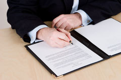 Signing the documents. A business man in a blue suit signing a contract on a wooden table Stock Photo