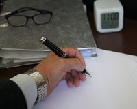 Signing documents and paperworks. Left handed businessman signing documents and paperworks, cropped image. Selective focus Stock Image