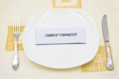 A Signing Family Finances on a Plate. A signing Family Finances on a white plate with a fork and a knife beside Stock Photography